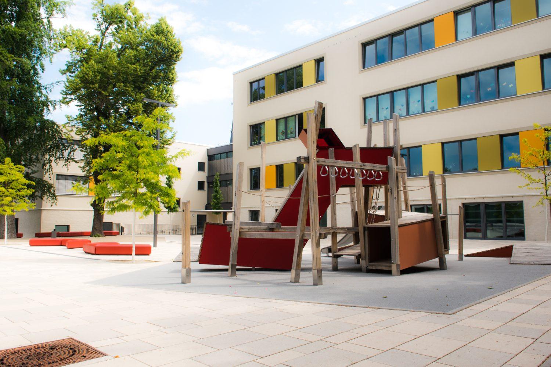 Schulgebäude, Spielplatz, Bäume