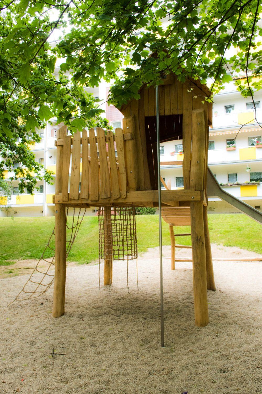 Spielplatzturm aus Holz, Sand, Baum, Wohnblock